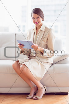 Happy businesswoman sitting on sofa using tablet pc