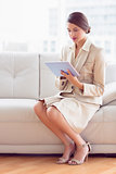 Pretty businesswoman sitting on sofa using tablet pc