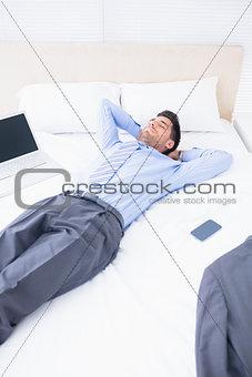 Sleeping businessman lying on his bed