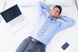 Happy businessman lying on his bed