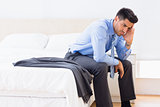 Frowning businessman sitting at edge of bed