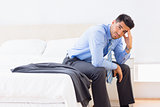 Frowning businessman sitting at edge of bed looking at camera