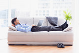 Businessman lying on sofa using his laptop