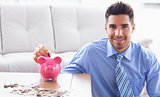 Cheerful businessman putting coins into piggy bank