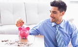 Handsome businessman putting coins into piggy bank
