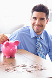 Handsome businessman putting coins into piggy bank looking at camera