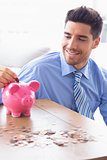 Handsome businessman putting change into piggy bank