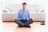 Handsome businessman sitting in lotus pose on the floor