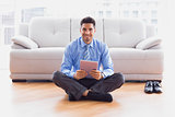 Businessman sitting on floor using tablet pc smiling at camera