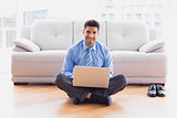 Businessman sitting on floor using laptop smiling at camera