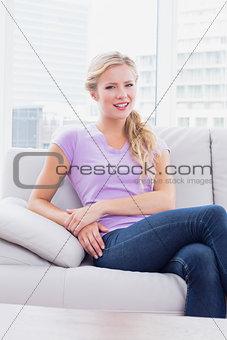 Beautiful blonde sitting on her sofa smiling at camera