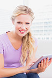 Smiling blonde sitting on her sofa using her tablet pc
