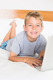 Blonde boy lying on bed using laptop smiling at camera