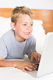 Blonde boy lying on bed using laptop