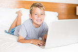 Happy blonde boy lying on bed using laptop