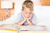 Happy blonde boy lying on bed reading a storybook