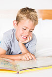 Cute blonde boy lying on bed reading a storybook