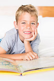 Cheerful blonde boy lying on bed reading a storybook