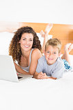 Cute blonde boy and mother lying on bed using laptop