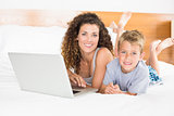 Smiling blonde boy and mother lying on bed using laptop