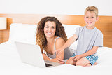 Happy blonde boy and mother on bed using laptop