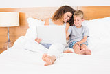 Mother and son sitting on bed using laptop