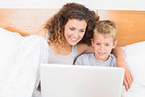 Cheerful mother and son sitting on bed using laptop