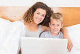 Pretty mother and son sitting on bed using laptop