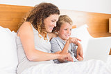 Smiling mother and son sitting on bed looking at laptop