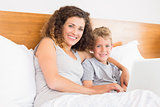 Smiling mother and son sitting on bed with laptop
