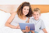 Smiling mother and son sitting on bed with tablet pc