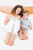 Happy mother and son sitting on bed with tablet pc