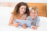 Happy mother and son lying on bed with tablet pc