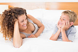 Happy mother and son lying on bed facing each other