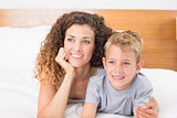 Happy mother and son lying on bed looking away