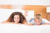 Smiling mother and son lying on bed looking at camera