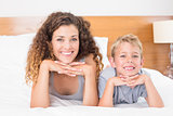 Cheerful mother and son lying on bed looking at camera