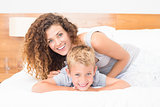 Happy mother and son posing on bed looking at camera