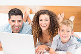 Cheerful family using laptop together on bed