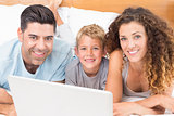 Happy young family using laptop together on bed