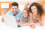 Smiling young family using laptop to shop online together on bed