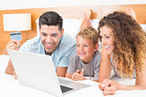 Happy young family using laptop to shop online together on bed