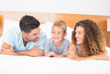 Happy young family lying on bed looking at each other