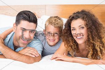 Smiling young family lying on bed looking at camera