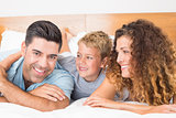 Smiling young family lying on bed together