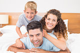 Cute young family smiling at camera on bed posing
