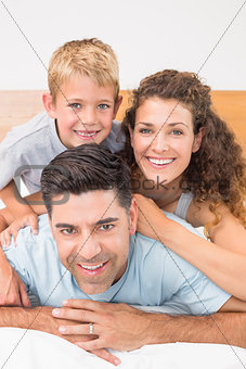 Attractive young family smiling at camera on bed posing