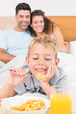 Cute young family having breakfast in bed