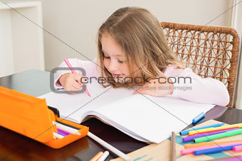 Cute little girl colouring at the table