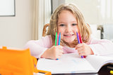 Cheerful little girl colouring at the table